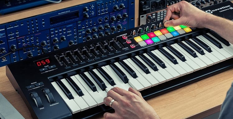 musician playing on keyboard with midi controller